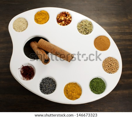 Spices palette. Creative concept using painting palette to show various spices and herbs - stock photo