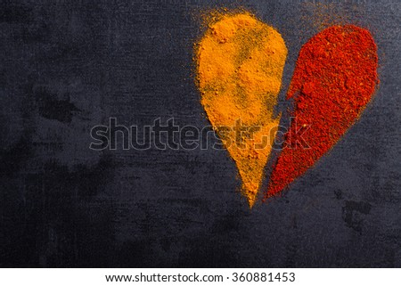 Spices paprika and turmeric piled on the pattern of broken heart with copy space. - stock photo