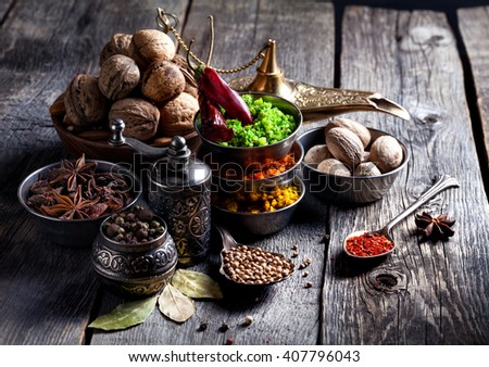Spices, pepper grinder, spoon with seeds at grey wooden background  - stock photo