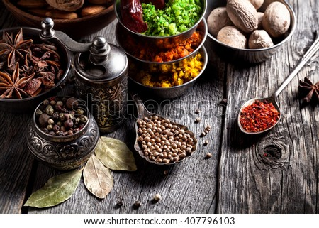 Spices, pepper grinder, spoon with seeds close up at grey wooden background  - stock photo
