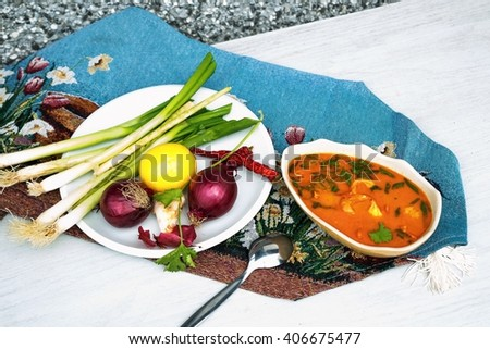Spicy asian soup with chicken and shrimps in beige bowl, onion,lemon and leaves in white plate, on rustic blue summer table-cloth on white table - stock photo