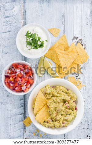 spicy avocado sauce and assorted sauces with corn chips on wooden table, vertical, top view - stock photo
