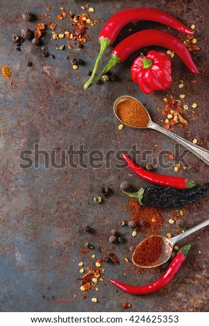 Spicy background with assortment of different hot chili and allspice peppers over old rusty iron background. Top view. With copy space - stock photo