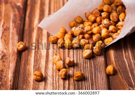 Spicy baked chickpeas in a metal pail on the wooden background - stock photo
