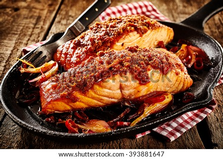 Spicy baked Mexican style fish with seasoning and fork in black cast iron griddle over napkin and rustic wooden table surface - stock photo