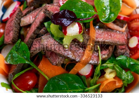 Spicy Beef Slices Meat Salad with Carrots, Tomatoes, Cucumber, Parsley, Radish and Salad leaves Spinach, rocket, red ruby chard  - stock photo