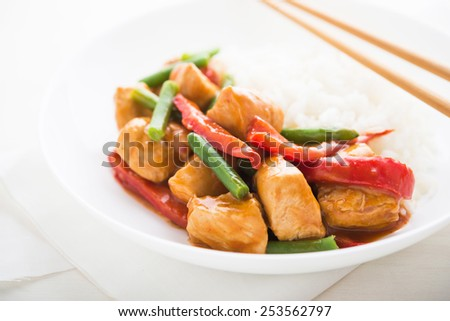 Spicy chicken with vegetables ( green beans and red pepper) and rice close up. Oriental food. - stock photo