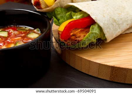 Spicy chicken wrap and pot of vibrant salsa. - stock photo