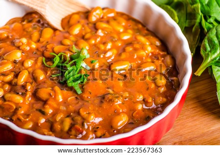 Spicy cowboy beans with chilli, jalapeno, scallions and bacon, Hassleback Potatoe with herbs - stock photo