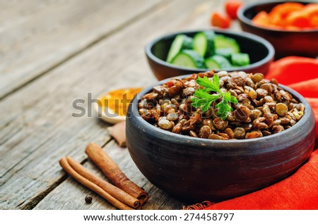 spicy curry cinnamon green lentils on a dark wood background. the toning. selective focus - stock photo