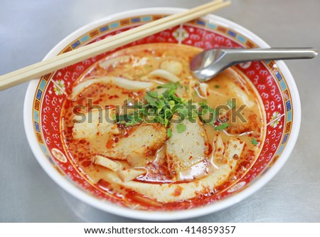Spicy fish noodle in the bowl with chopsticks and spoon - stock photo