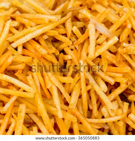 spicy french fries fast food snack like background from India, close up  - stock photo