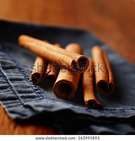 Spicy fresh cinnamon sticks used as a seasoning and flavouring in cooking lying on a napkin with the rolled end of the bark facing the camera - stock photo