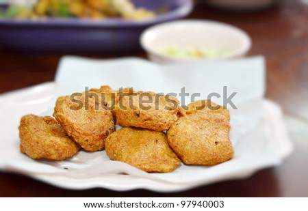 Spicy fried fish cake (Tod Mun Pla) served with cucumber in sweet sauce - stock photo