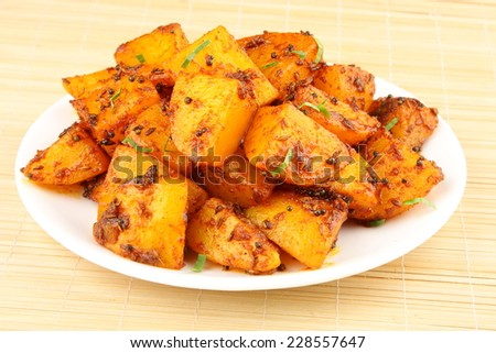 Spicy fried potatoes with herbs and spices served in white plate. Shallow depth of field photograph - stock photo