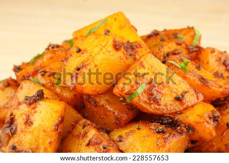 Spicy fried potatoes with herbs and spices. Shallow depth of field photograph - stock photo