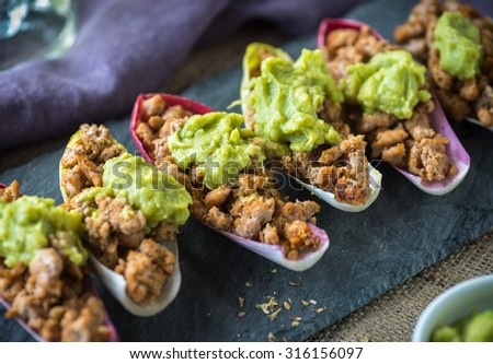 Spicy ground turkey boats with guacamole in radicchio - stock photo
