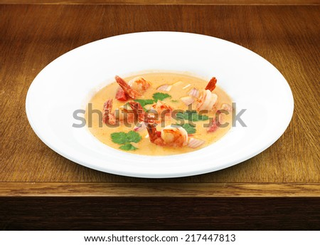 Spicy healthy thai tom yum soup served with royal shrimps and herbs. Wooden table - stock photo