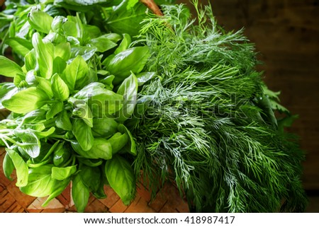 Spicy herbs: green basil, mint, coriander, dill, cilantro, parsley in a wicker basket on a vintage wooden background, selective focus - stock photo