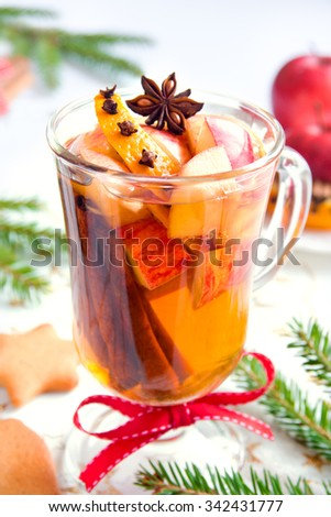 Spicy hot drink (cider, punch, tea) with apple, orange, cinnamon, star anise for Christmas and winter holidays - stock photo