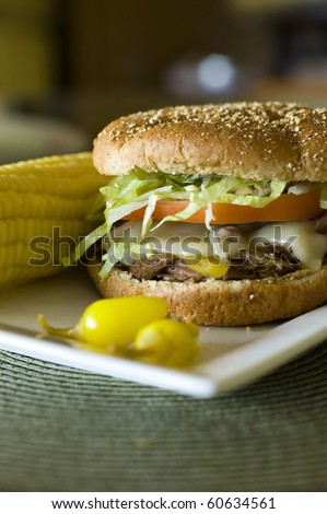 Spicy Italian Beef Sandwich on a Toasted Whole Wheat Bun with Peperoncini Peppers and Corn on the Cob - stock photo