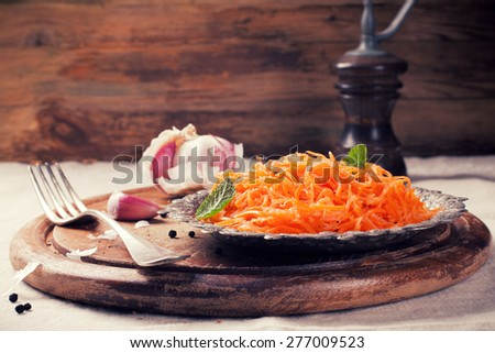 Spicy Korean style carrot salad on metal plate with spices. Selective focus. Rustic style. Toned - stock photo