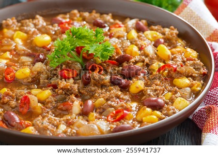 spicy Mexican dish chili con carne in a brown pottery plate, close-up, horizontal - stock photo