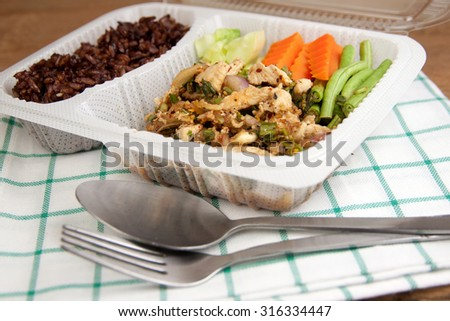 Spicy minced chicken salad and brown rice thai cuisine put in a modern plastic box - stock photo