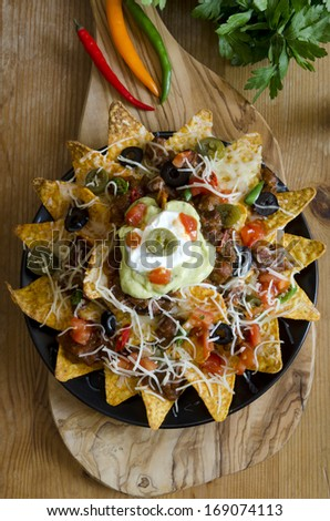 Spicy nachos with beef, chilli peppers, sour cream and guacamole - stock photo