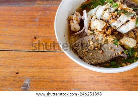 Spicy Noodle in a white bowl on wooden background. The favorite meal for lunch. Thailand food. - stock photo