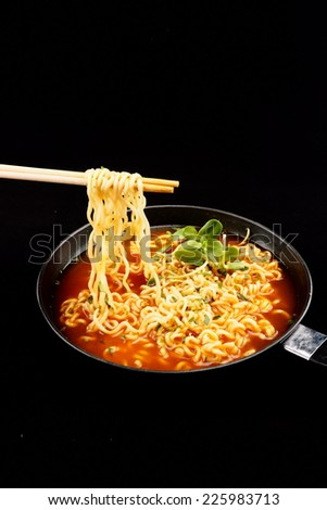 spicy noodle soup on black background - stock photo