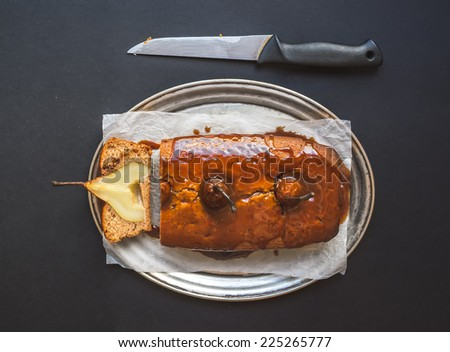 Spicy pear cake with caramel topping on a silver dish on dark background - stock photo