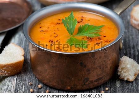 Spicy red lentil soup in a copper saucepan, close-up, horizontal - stock photo