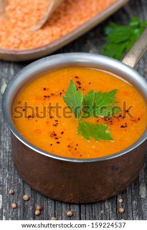 Spicy red lentil soup in a copper saucepan, close-up, top view, vertical - stock photo