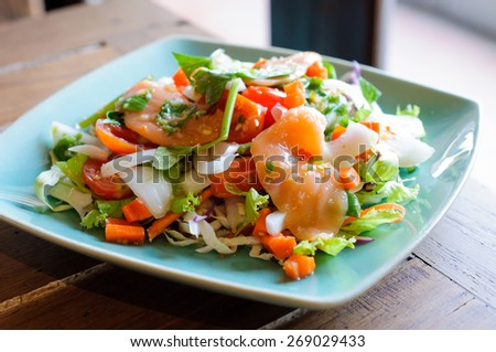 Spicy salmon salad with mixed vegetable and herb - stock photo