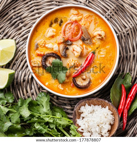 Spicy Thai soup Tom Yam with Coconut milk, Chili pepper and Seafood - stock photo