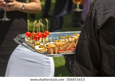 spiked cocktail and finger food snacks - stock photo