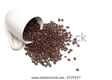 spill the beans - white coffee cup with spilt whole coffee beans, a high-key closeup isolated on white - stock photo