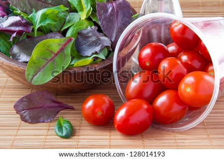 Spilled cherry tomatoes and salad - stock photo