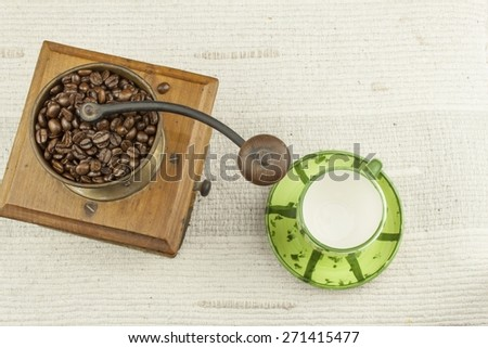 Spilled coffee beans, coffee mug, old coffee grinder - stock photo