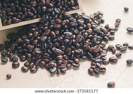 Spilled coffee beans from the wooden box on the leather texture. - stock photo