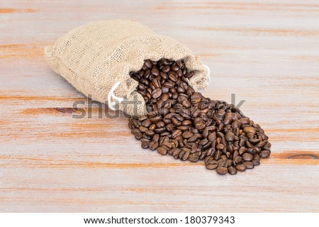 spilled coffee beans out of a burlap sack on a sun bleached wooden background - stock photo