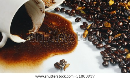 Spilled coffee with beans and cup - stock photo
