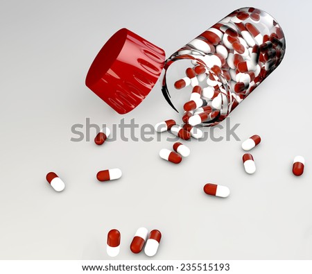 Spilled red and white aspirin pills and bottle on gray background - stock photo