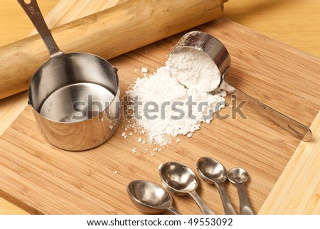 Spilled Scoop of Cooking Flour with Miscellaneous Baking Tools - stock photo