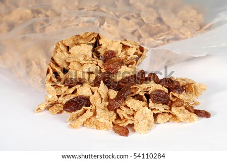 spilling bran and raisin cereal - stock photo