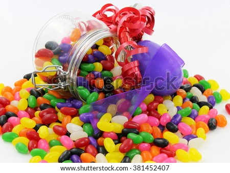 Spilt Jelly Beans in Glass Jar with large Purple Plastic Easter Egg and Red and Purple Ribbon - stock photo