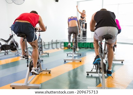 Spin class working out with motivational instructor at the gym - stock photo