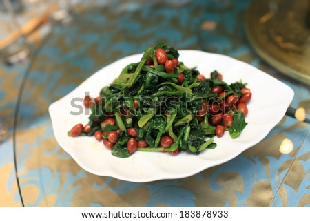 Spinach and crispy peanuts salad with aged vinegar in a chinese restaurant - stock photo