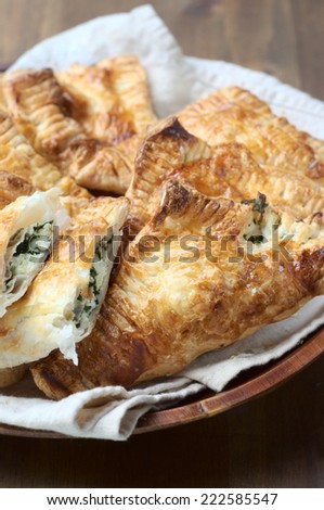 Spinach and ricotta pasties on a bamboo plate and on a wooden background - stock photo